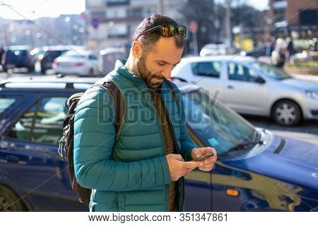 Man Looking At Cell Phone. Man Looking At Cell Phone While Walking On Street. Man Reading Message On