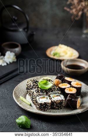 Set Of Sushi And Maki With Soy Sauce Over Black Background. Top View With Copy Space