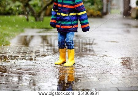 Close-up Of Kid Wearing Yellow Rain Boots And Walking During Sleet, Rain And Snow On Cold Day. Child
