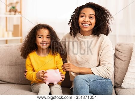 Personal Savings. Happy Mother And Daughter Holding Piggybank Embracing Sitting On Sofa At Home