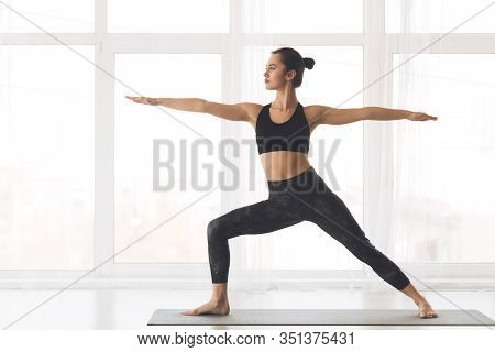 Virabhadrasana Pose. Fit Girl Standing By Window In Warrior Pose In Modern Studio, Copyspace, Full L