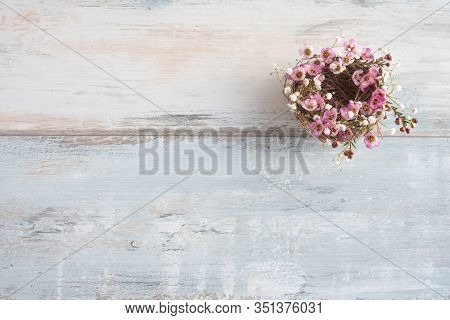 Little Flower Wreath On Gray Vintage Planks. Pink Spring Flowers In A Nest. Flat Lay Photography Wit