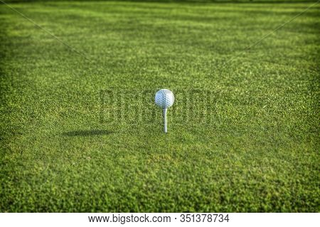 Single Golf Ball Balanced On A White Tee, With Lush Green Grass At The Tee Box, With A Long Shadow