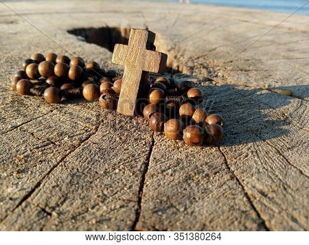 Rosary Beads On Rustic Wooden Round Table With Jesus Christ Holy Cross Crucifix Backgrounds. Catholi