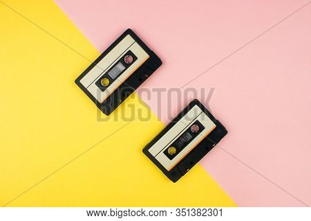 Retro Audio Cassettes Flat Lay On Colorful Yellow And Pink Background Top View With Copy Space. Crea