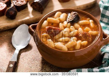 Typical Spanish Fabada Asturiana In Crockpot On Wooden Table