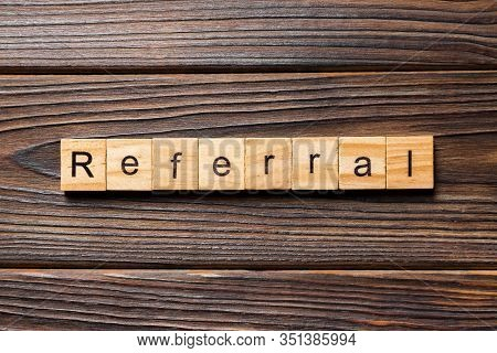 Referral Word Written On Wood Block. Referral Text On Wooden Table For Your Desing, Top View Concept