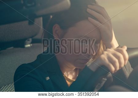Disappointed Businesswoman In Car, Gripping The Vehicle Steering Wheel And Holding Her Head In Disbe