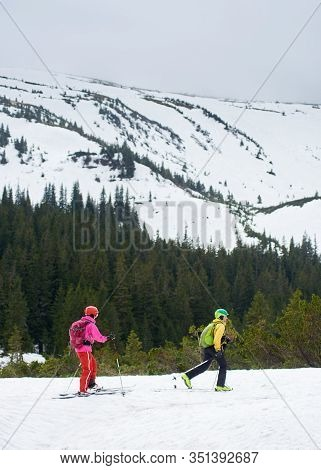 Side View Couple Of Cross Country Skiers Male And Female With Backpacks Walking And Exercising On Sk