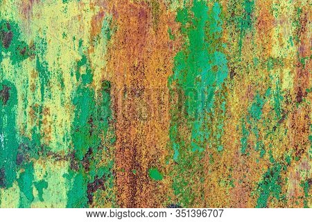 Part Of Old Metal Exterior Doors. Yellow And Green Painted, In Bouncing Layers,  Rusty Surface With