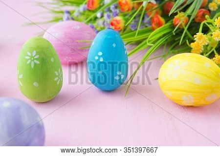 Easter Eggs With Wild Flowers On A Wooden Pink Table Background