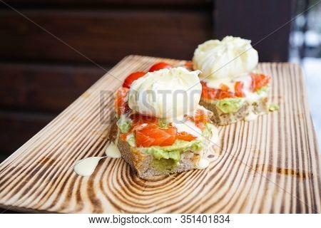 Benedict Eggs With Avocado And Smoked Salmon, Hollandaise Sauce On A Wooden Board, Close-up.