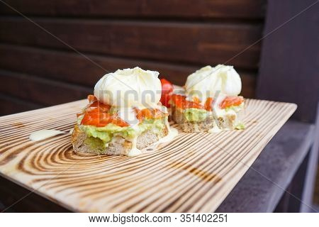 Benedict Eggs With Avocado And Smoked Salmon, Hollandaise Sauce On A Wooden Board