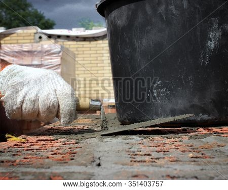 Bricklayers Hands With In Masonry Trowel Bricklaying New House Wall On Foundation. Close Up Of Indus