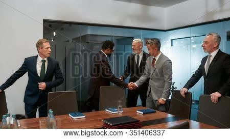 African And Asian Businessmen In Formal Wear Shaking Hands After Signing The Agreement While Standin