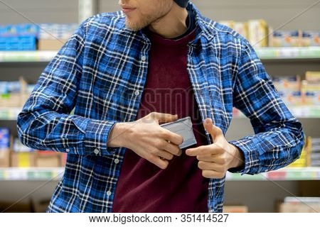 Kleptomania Concept, A Man In The Grocery Store Stealing Food And Put It In The Pocket