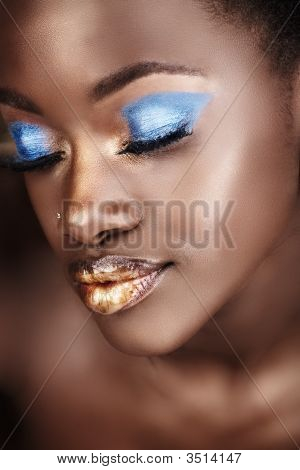 African woman with gold and blue metallic make-up and full shiny lips poster