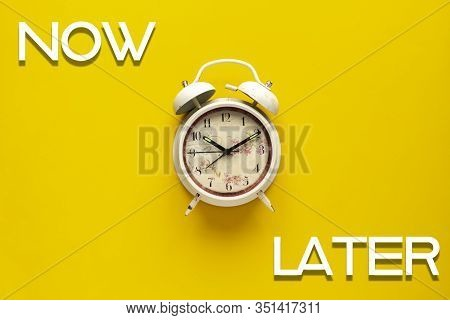 A Simple Retro Alarm Clock On Color Background With Words Now And Later, Motivation Idea