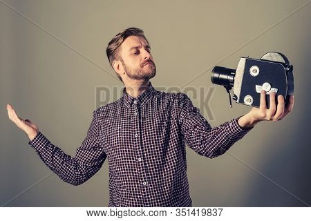 Young Attractive Cameraman In A Plaid Shirt Takes Himself Off To An Old Movie Camera. Selffi Concept