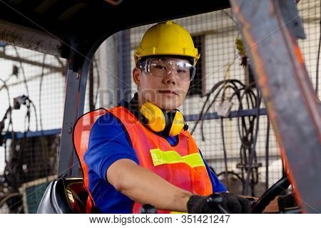 A Man With Yellow Safety Helmet And Goggles Driving A Forklift Or Reach  Truck  At The Logistics War