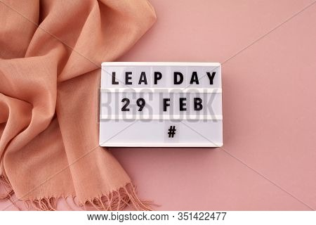 White Block Calendar Present Date 29 And Month February And Scarf On Pink Background. Leap Day