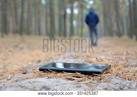 Young Man Loses His Smartphone On Russian Autumn Fir Wood Path. Carelessness And Losing Expensive Mo