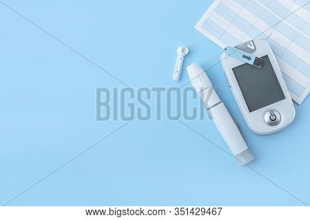 Diabetes. Self-monitoring Of Blood Glucose. Lancet, Glucometer, Control Book On A Blue Background. D