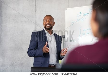 Mature african american coach explaining strategy to his team with copy space. Successful businessman presenting new project to employees during meeting room. Conference speaker talk to audience.