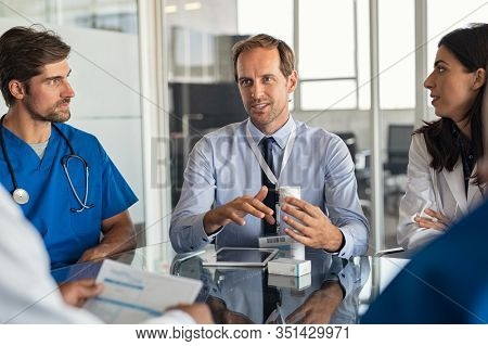 Confident representative pharmaceutical showing new medicines to a team of doctor and nurse in hospital. Mature specialist man showing bottle of pills and explaining drug dosage to a group of doctors.