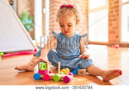 Beautiful caucasian infant playing with toys at colorful playroom. Happy and playful with wooden train pieces at kindergarten.