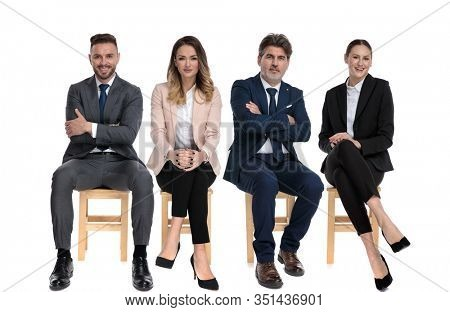 Team of 4 happy businessmen smiling and holding their arms crossed, on legs or chin while sitting on chairs on white studio background