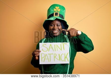 Plus size african american woman wearing green hat holding banner on saint patricks day with surprise face pointing finger to himself