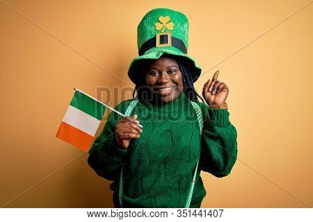Plus size african american woman wearing green hat holding irish flag on saint patricks day surprised with an idea or question pointing finger with happy face, number one