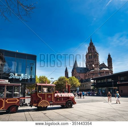 Mainz, Germany - August 12, 2018: Tourist Train In Old Town Of Mainz With Mainz Cathedral In The Bac