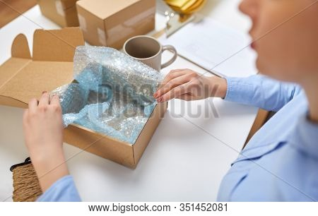 delivery, mail service, people and shipment concept - close up of woman packing mug into parcel box and it wrapping into protective bubble wrap at post office