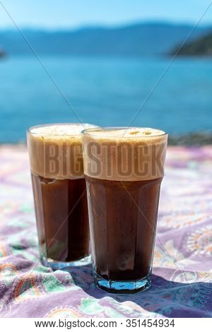 Two Glasses Of Greek Cold Iced Instant Coffee With Foam Frappe On Sunny Beach