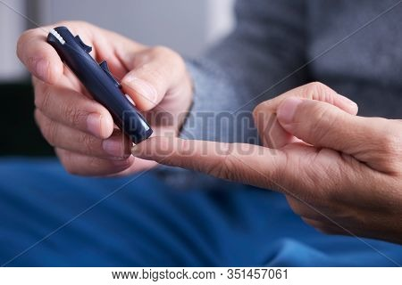 closeup of a caucasian man about to measure his blood glucose level in a glucose meter by pricking his finger with a fingerstick