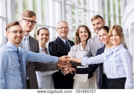 corporate, people and teamwork concept - happy business team stacking hands at office