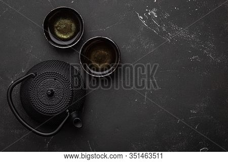 Traditional Asian Tea In Black Cast Iron Vintage Teapot With Two Cups On Dark Stone Table, Top View.