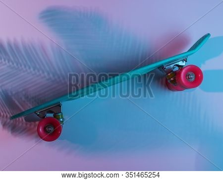 Plastic Mini Cruiser Board On Background With Shadow From Palm Leaves. Neon Gradient Ligh. Top View