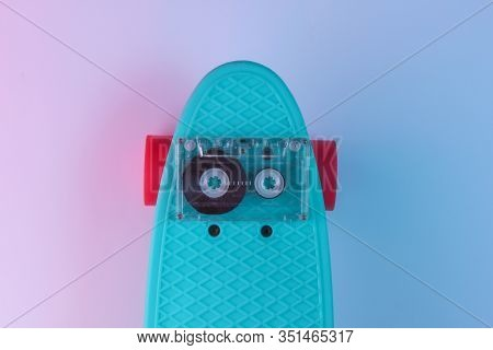 Retro 80s Objects. Plastic Mini Cruiser Board And Audio Tape On Background With Blue Pink Neon Gradi