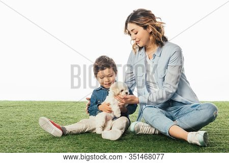 Smiling Mother And Son Holding Havanese Puppy Isolated On White