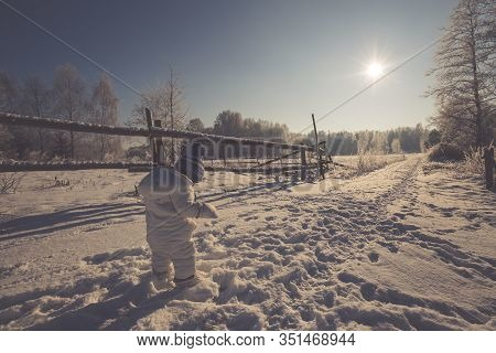Little Child In Snow Field. Little Child Boy Walking In Winter Field