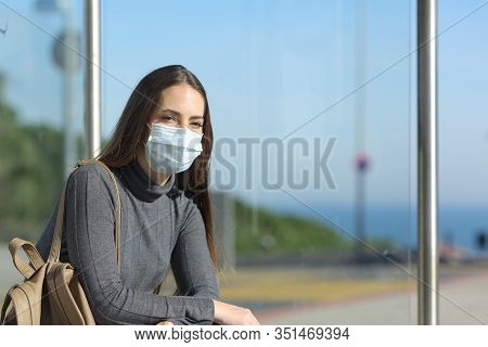 Girl Wearing A Mask Preventing Contagion Sitting Waiting In A Bus Stop