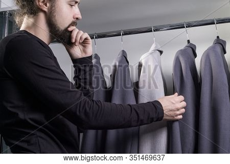 Close-up Portrait Of A Young Bearded Guy, Millennial, In A Mens Clothing Store, Chooses A Business S