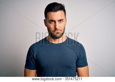Young handsome man wearing casual t-shirt standing over isolated white background depressed and worry for distress, crying angry and afraid. Sad expression.