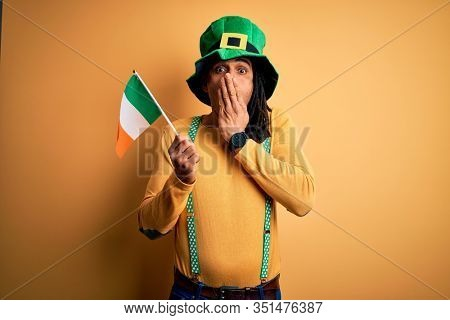 African american man wearing green hat holding irish ireland flag celebrating saint patricks day cover mouth with hand shocked with shame for mistake, expression of fear, scared in silence