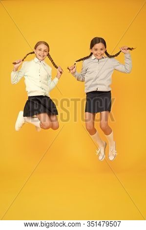 Beautify Your Hairstyle Today. Adorable Small Girls With Long Hairstyle Jumping On Yellow Background