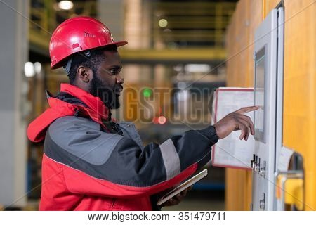 Horizontal medium side view portrait of professional Black male factory engineer setting up equipment