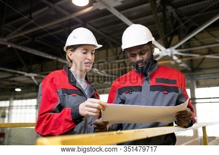 Horizontal low angle portrait shot of two professional factory engineers working together on new project